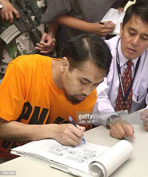 Jailed Indonesian Fathur Rohman al Ghozi identifies portrait sketches of suspected terrorists before state prosecutors at the Philippine Justice...