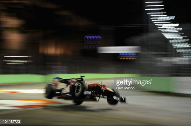 Jaime Alguersuari of Spain and Scuderia Toro Rosso goes airborne over a curb during the Singapore Formula One Grand Prix at the Marina Bay Street...