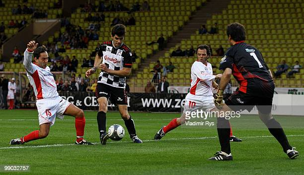 Jaime Alguersuari of Spain and Scuderia Toro Rosso shoots on Antoine Ettori as Loris Capirossi and Alex Caffi defend during the football charity...