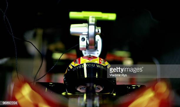 Jaime Alguersuari of Spain and Scuderia Toro Rosso sits in his car in the garage during winter testing at the Circuito De Jerez on February 19 2010...