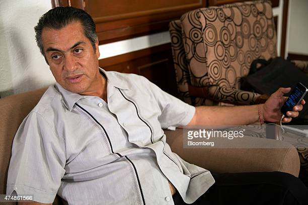 Jaime El Bronco Rodriguez independent candidate for governor of Nuevo Leon checks his mobile phone during an interview in Monterrey Mexico on Monday...