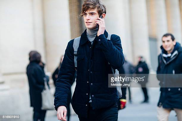 Jaime Ferrandis talks on his phone and wears a black jacket and gray turtleneck after the Lemaire show on Day 1 of Paris Fashion Week Mens on January...