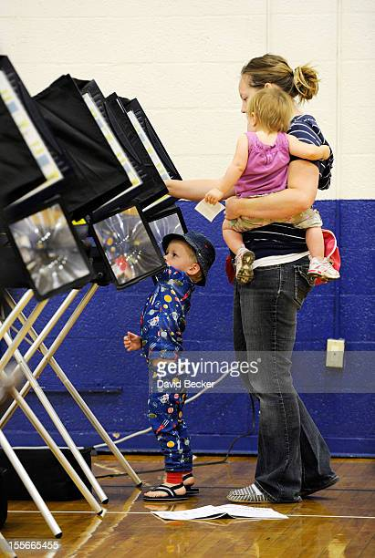 Jaime Lea with her children one yearold Scarlett and Zackary casts her ballot at John Fremont Middle School on November 6 2012 in Las Vegas Nevada...