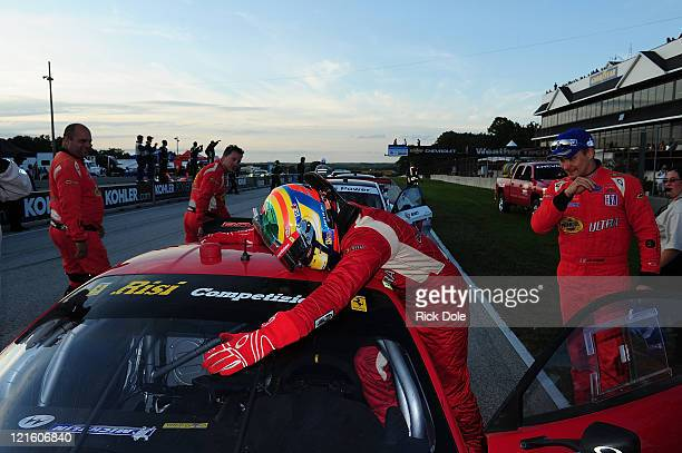 Jaime Melo of Brazil hugs his GT class winning Risi Competizione Ferrari 458 Italia following the American Le Mans Series Time Warner Cable Road Race...