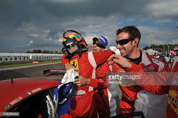 Jaime Melo of Brazil is hugged by codriver Gianmaria Bruni of Italy as they celebrate their victory in the GT class in the Risi Competizione Ferrari...