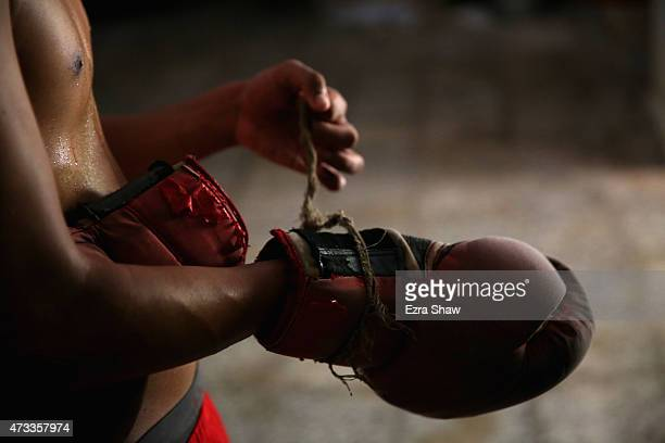 Jaime Poradius 16yearsold takes off his boxing gloves after a training session at the Salvador Allende Sports Complex on May 9 2015 in Alamar Cuba...