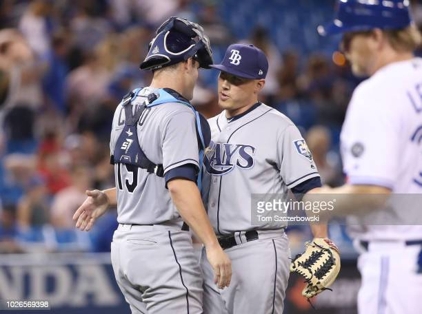 Jaime Schultz of the Tampa Bay Rays celebrates their victory with Nick Ciuffo during MLB game action against the Toronto Blue Jays at Rogers Centre...