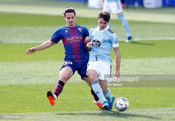 Jaime Seoane of SD Huesca battles for possession with Denis Suarez of Celta Vigo during the La Liga Santander match between SD Huesca and RC Celta at...