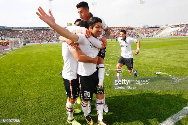 Jaime Valdes of ColoColo celebrates with teammates after scoring the second goal of his team during a match between ColoColo and U de Chile as part...