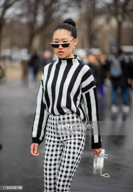 b0179d87c8 Jaime Xie is seen wearing black white striped jumper plaid pants bag  outside Chanel during Paris