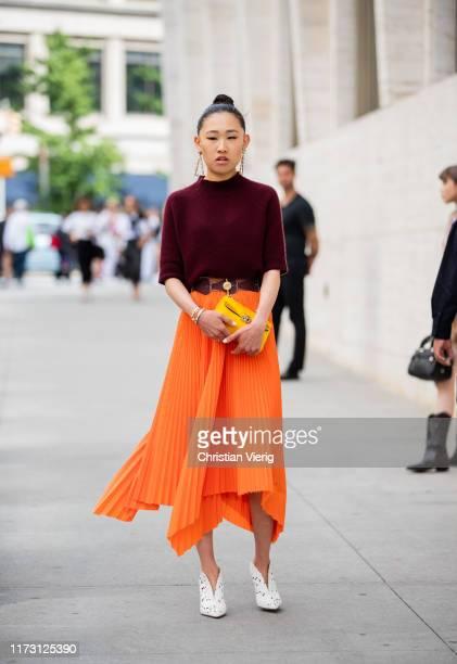 Jaime Xie is seen wearing orange pleated skirt, bordeaux knit outside Longchamp during New York Fashion Week September 2019 on September 07, 2019 in...