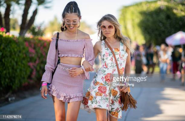 Jaime Xie is seen wearing pink cropped top and skirt and Erica Pelosini wearing dress with floral print bag with fringes at the Revolve Festival...