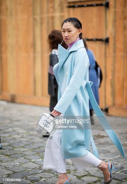 Jaime Xie is seen wearing pink turtleneck blue coat white Cahnel bag white wide leg pants outside Thom Browne during Paris Fashion Week Womenswear...