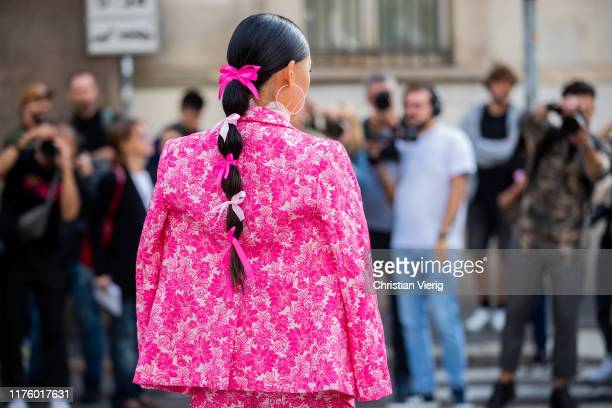 Jaime Xie seen with bows in her hair wearing pink jacket and pants with floral print outside the Blumarine show during Milan Fashion Week...
