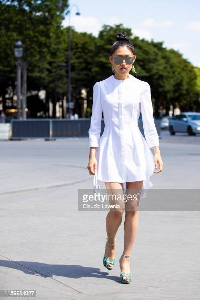 Jaime Xie, wearing Alexander McQueen white dress, Charlotte Olympia shoes, Jacquemus white bag and Chanel sunglasses, is seen outside Chanel show...