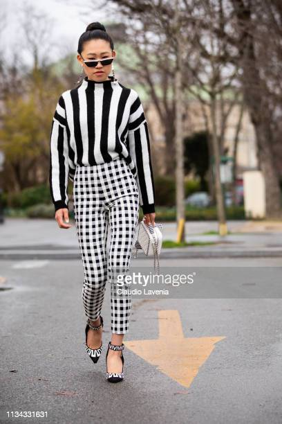 Jaime Xie wearing black white striped jumper plaid pants and Chanel bag is seen outside Chanel on Day 9 Paris Fashion Week Autumn/Winter 2019/20 on...