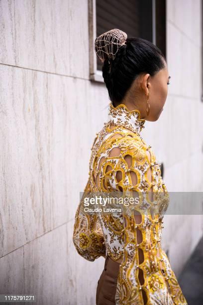 Jaime Xie, wearing brown Max Mara pants, Zimmerman top and row bag, poses outside the Max Mara show during Milan Fashion Week Spring/Summer 2020 on...