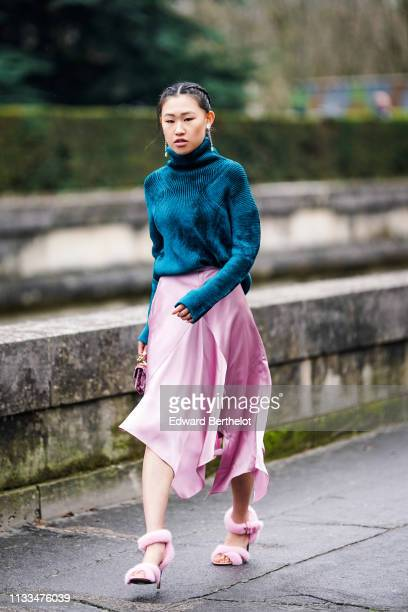 Jaime Xie wears a blue wool turtleneck pullover, a pink silky skirt, pink fluffy shoes, earrings, a pink bag, outside Valentino, during Paris Fashion...