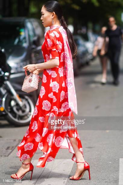 Jaime Xie wears Dior earrings a long red floral print dress with a pink lavaliere red shiny anklestrap sandals a glittering Lady Dior handbag outside...