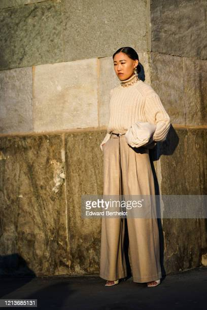 Jaime Xie wears earrings, a necklace, a beige ribbed turtleneck, a thin black belt, light brown pleated wide-legs full-length pants, white sandals, a...