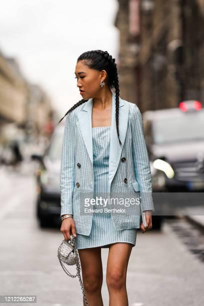 Jaime Xie wears earrings, bracelets, a light blue leather studded jacket, a light blue leather studded bustier mini dress, a glittering bejeweled...