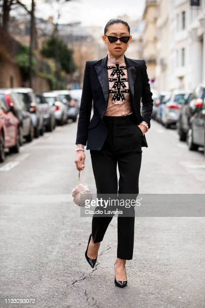 Jaime Xie wears earrings sunglasses a glittering strass clutch a peachcolor lace top a black paddedshoulder jacket with strass black straps on the...