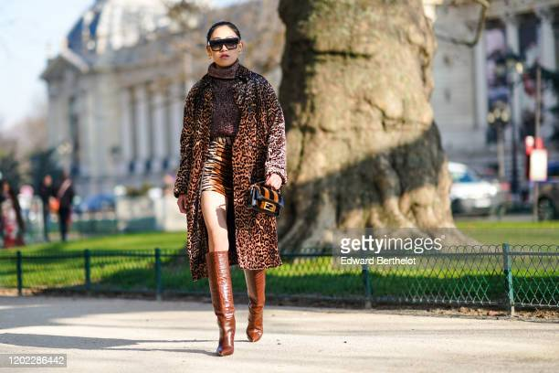 Jaime Xie wears sunglasses, a turtleneck wool glitter purple pullover, a leopard print long coat, a tiger print brown mini skirt, a Fendi bag, brown...