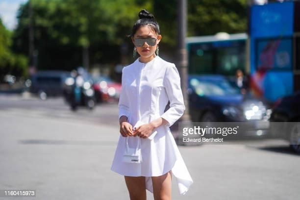 Jaime Xie wears sunglasses earrings a white dress a white Jackquemus mini bag outside Chanel during Paris Fashion Week Haute Couture Fall/Winter...