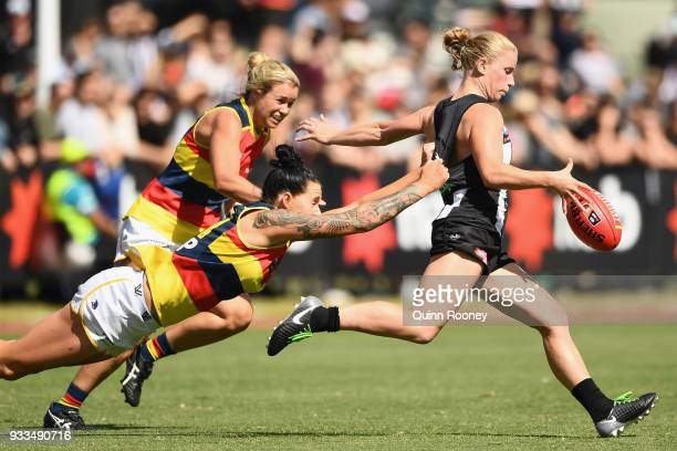 Jaimee Lambert of the Magpies kicks whilst being tackled by Rhiannon Metcalfe of the Crows during the round seven AFLW match between the Collingwood...