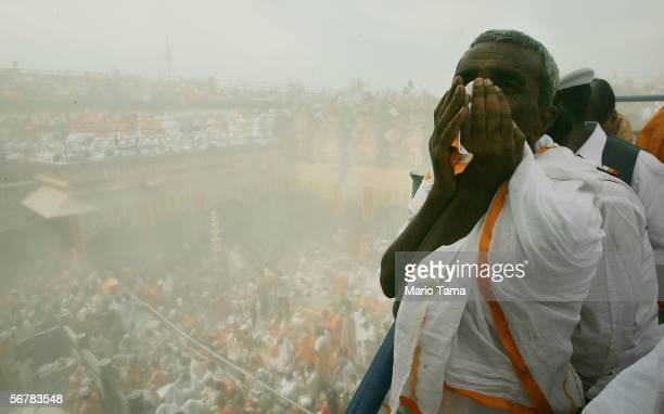 Jain devotee covers his face as flour is poured over the monolithic statue of Jain sage Gomateswara during the first day of the Mahamastak Abhisheka...