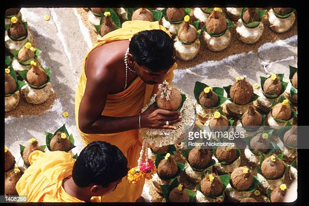 A Jain devotee places a coconut on top of a kalasha at the monolithic statue of Bhagwan Bahubali during the Mahamastakabhisheka ceremony December 19...