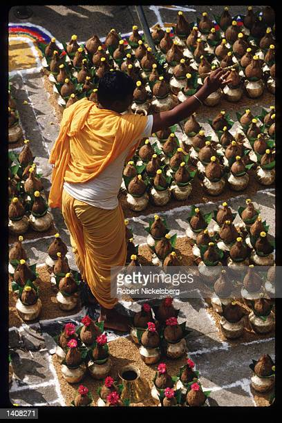 A Jain devotee stands among kalashas at the monolithic statue of Bhagwan Bahubali during the Mahamastakabhisheka ceremony December 19 1993 in...