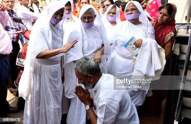 Jain devotee takes the blessings of Sadhvis on the occasion of Mahavir Jayanti at Freedom Park on March 29 2018 in Bengaluru India This day marks the...
