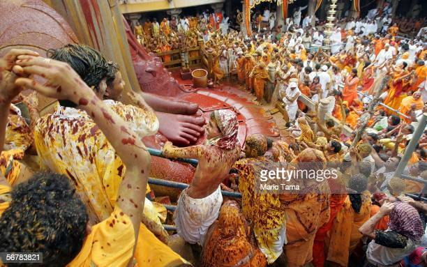 Jain devotees are soaked in liquid vermillion and saffron as they look up at the monolithic statue of Jain sage Gomateswara during the first day of...