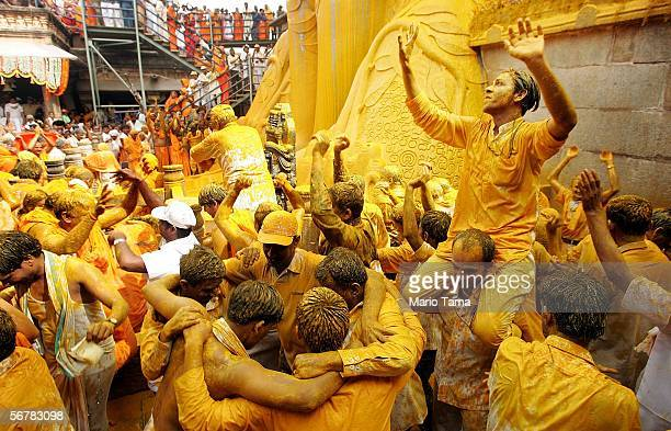 Jain devotees dance as they are soaked in liquid saffron as it poured over the monolithic statue of Jain sage Gomateswara during the first day of the...