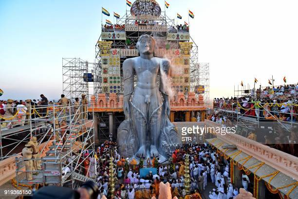 TOPSHOT Jain devotees pour milk on the 57 fthigh monolythic statue of Lord Bahubali during the start of 88th 'Mahamastakabhisheka' the 'grand head...