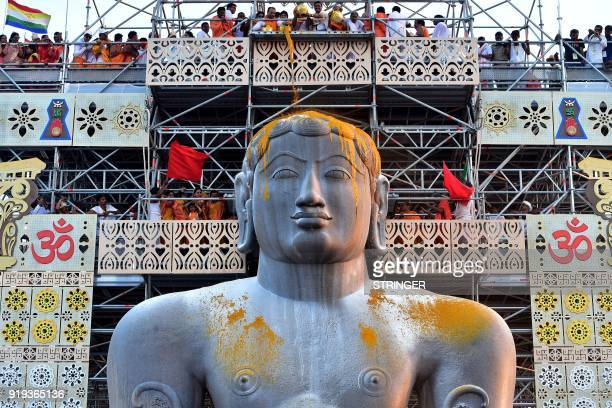 Jain devotees pour turmeric paste on the 57 fthigh monolythic statue of Lord Bahubali during the start of 88th 'Mahamastakabhisheka' the 'grand head...