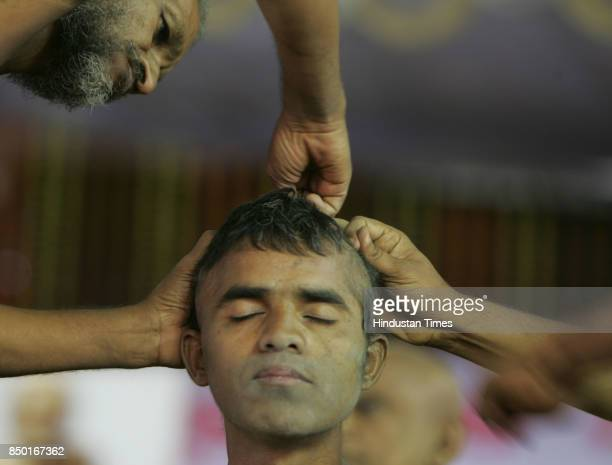 Jain monks perform `Keshalochan' hair removing ritual on a Jain shravak who took a muni diksha at the Jain digambar muni diksha grahan programme held...
