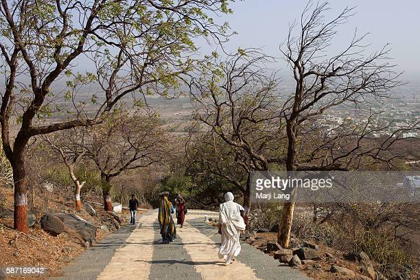 Jain nun and pilgrims walking down the path from Palitana temples on Shatrunjaya hill Gujarat India Palitana is the worlds only mountain that has...