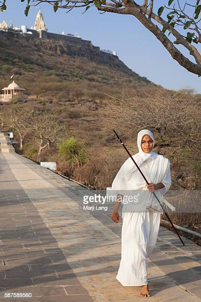 Jain nun walking down the path from Palitana temples on Shatrunjaya hill Gujarat India