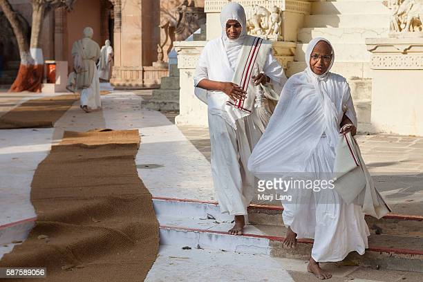 Jain nuns walking down the path from Palitana temples on Shatrunjaya hill Gujarat India