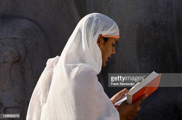Jain pilgrim is reciting religeous texts at the feet of the gigantic staue of Gomateshwara in Sravanabelagola