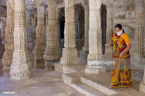 Jain pilgrim with traditional mask carrying offering at The Ranakpur Jain Temple at Desuri Tehsil in Pali District Rajasthan India