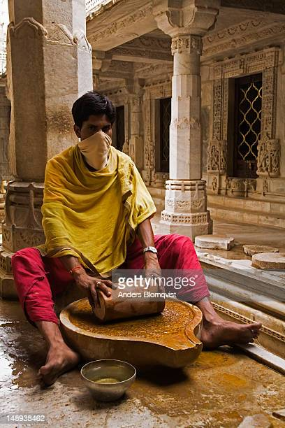 Jain priest grinding sandalwood log into paste to be used in religious ceremonies, Chaumukha Mandir.