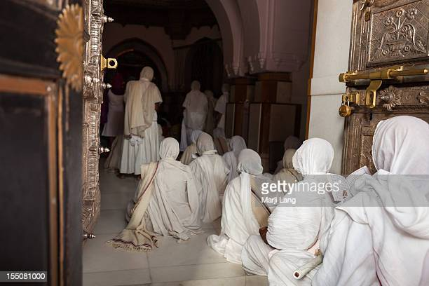 jain sadhvis praying inside shatrunjaya temple - palitana stock photos and pictures