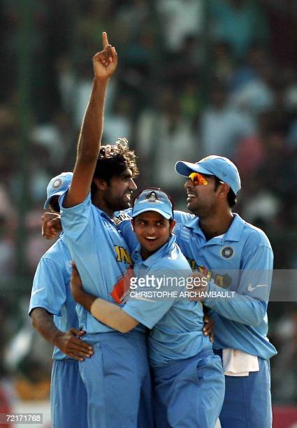 Indian cricketer Munaf Patel celebrates with teammates Suresh Raina and Yuvraj Singh after his dismissal of unseen England batsman Kevin Pietersen...
