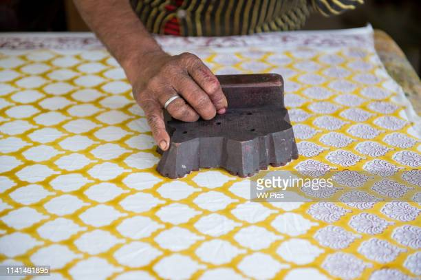 Jaipur India Indian man stamping pattern on fabric