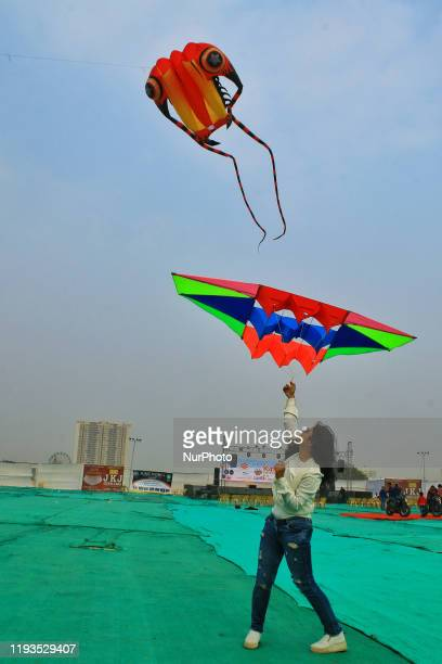 Woman fly Decorative kites during the Kite Festival on the occasion of Makar Sakranti Festival celebration in Jaipur RajasthanIndia 13 Jan2020
