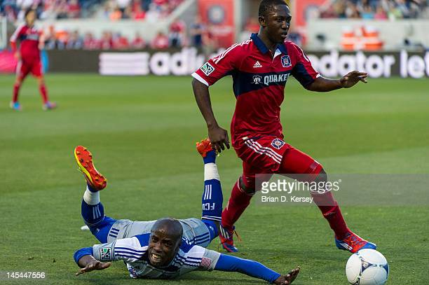 Jair Benitez of FC Dallas falls as he an Patrick Nyarko of the Chicago Fire go for the ball at Toyota Park on May 23 2012 in Bridgeview Illinois The...