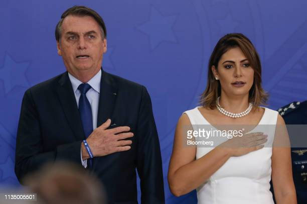 Jair Bolsonaro Brazil's president left and wife Michelle Bolsonaro Brazil's first lady sing the national anthem during a ceremony with military...